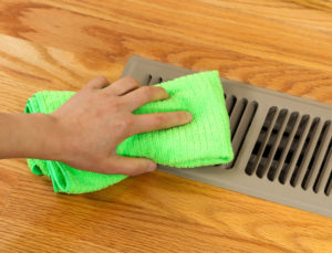 22709989 - horizontal photo of female hand cleaning outside grill plate of heater floor vent