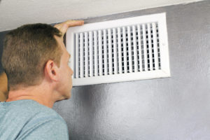 53766988 - mature man examining an outflow air vent grid and duct to see if it needs cleaning. one guy looking into a home air duct to see how clean and healthy it is.